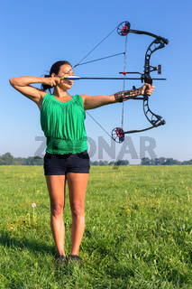 Young woman shooting arrow of compound bow