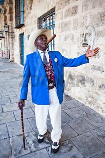 Havana, Cuba - December 12, 2016:  Traditional Cuban man with walking cane posing for photos while smoking big cuban cigar in Old Havana, Cuba.