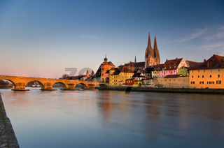 Long exposure of Regensburger old town with stone bridge, danube and cathedral in afternoon light