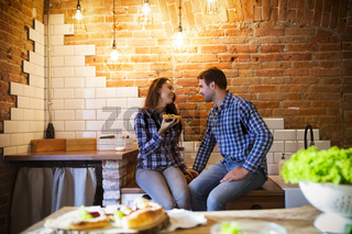 Young man and woman cooking and eating together at kitchen
