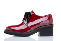 Cherry red lacquered shoes on a white background