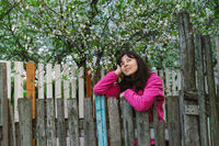 young woman standing by old fence and dreamy looking