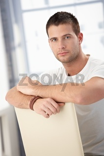Handsome man sitting conversely on chair