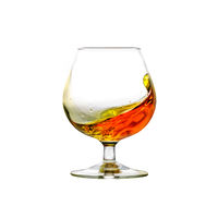 A filled cognac snifter with moving liquid