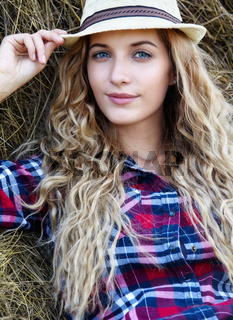 Young blonde  blue-eyed country girl in hat near haystacks