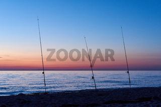 Drei Angelruten am Strand in der Dämmerung