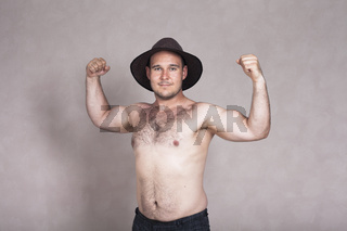 Shirtless man in hat posing and showing his strong body