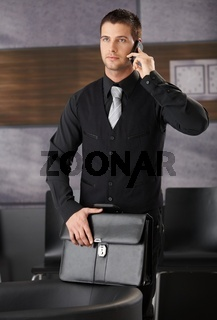 Handsome businessman in office lobby with mobile