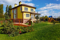 Exterior of luxury home with green yard, wooden bridge and colorful children playground