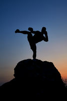 Dark silhouette of a muscular male boxer outdoors on sunset