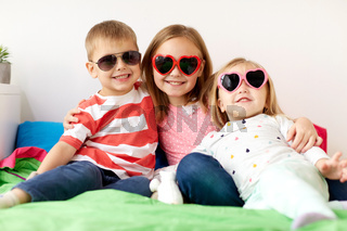 happy little kids in sunglasses at home