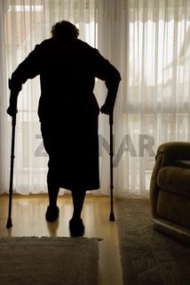 Eine gebrechliche Frau läuft mit Krücken in ihrer Wohnung