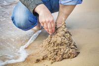 Man built sand castle near sea