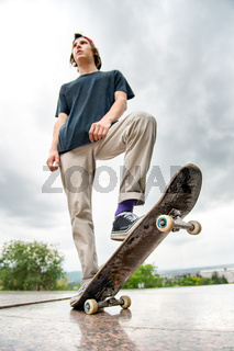 A young skater stands with a skateboard on the background of the landscape of the city