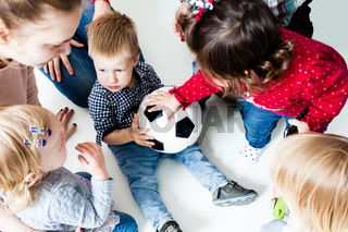 Children stretch to the ball
