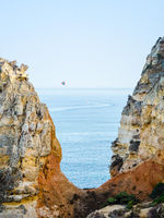 Parasailing, also known as parascending or parakiting at the coasts of the Algarve in Lagos, Portugal. Surrounded with yellow, orange limestones.