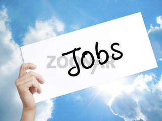Jobs Sign on white paper. Man Hand Holding Paper with text. Isolated on sky background
