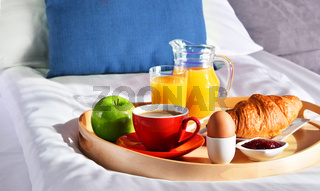 Breakfast on tray in bed in hotel room.