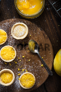 filling lemon and custard mini tarts on wooden board