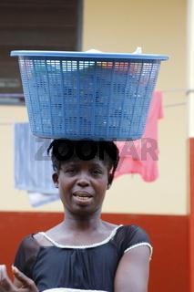 Junge Frau transportiert Wäschekorb auf dem Kopf