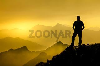Man standing on summit enjoying sunrise and spectacular layered mountain range silhouettes.