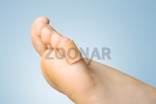 Closeup of a plaster on female toe