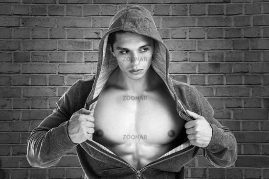 Bodybuilder Muskeln Mann stark muskulös jung Jacke schwarzweiß Ziegelwand
