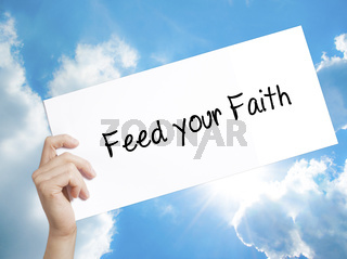 Feed your Faith Sign on white paper. Man Hand Holding Paper with text. Isolated on sky background