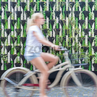 Woman riding bycicle by green urban vertical garden wall.