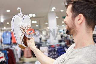Junger Mann beim Shopping nach Schuhen