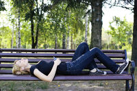 Woman relaxing on a bench, listening to music.