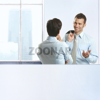 Two coworkers chatting in office