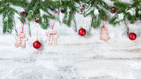 Snowy Christmas branches with hanging ornaments on rustic white wooden background
