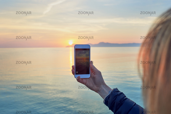 Young woman taking a photo of a colorful ocean sunset