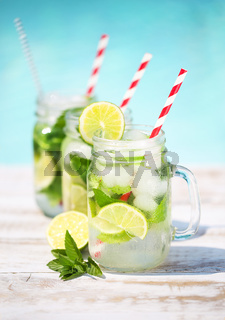 Glasses of lime lemonade near pool