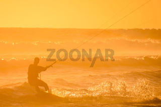 Surfer at sunset on a calm ocean