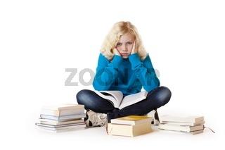Schulmädchen sitzt müde und frustriert am Boden und lernt für de