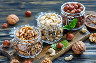 Different varieties of nuts in glass jars.