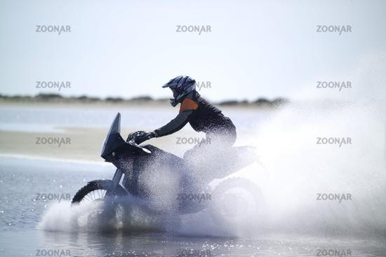 Motorradfahrer fährt durch Wasser