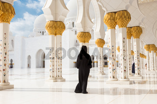 Arabic woman in black burka in Sheikh Zayed Grand Mosque, Abu Dhabi, UAE.