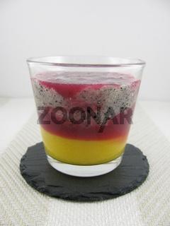 Granatapfelsaft, pürierte Drachenfrucht und Mangomus im Glas