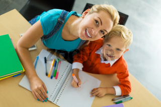 Cute boy and his mom sit at the desk in the office and hold pencils