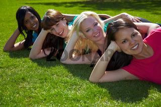 Vier Frauen liegen im Park