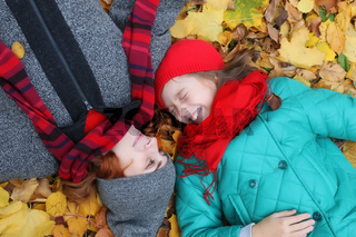 daughter and mother lay on ground leaves autumn