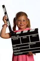 Young girl holding a clapperboard