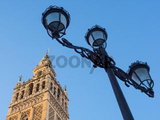 Giralda der Kathedrale von Sevilla und Straßenlaterne vor blauem Himmel