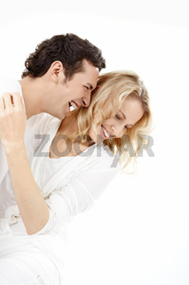 The enamoured couple laughs on a white background
