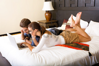 Young couple using a laptop in a asian hotel room