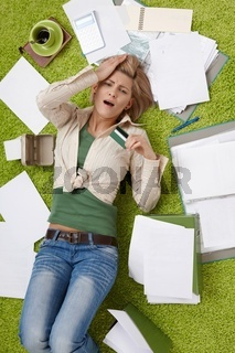 Shocked woman on floor with bills