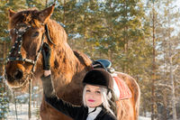 Young beautiful girl jockey and horse in winter forest